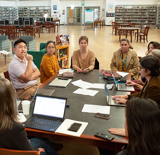 a group on people talking at a conference table in a library