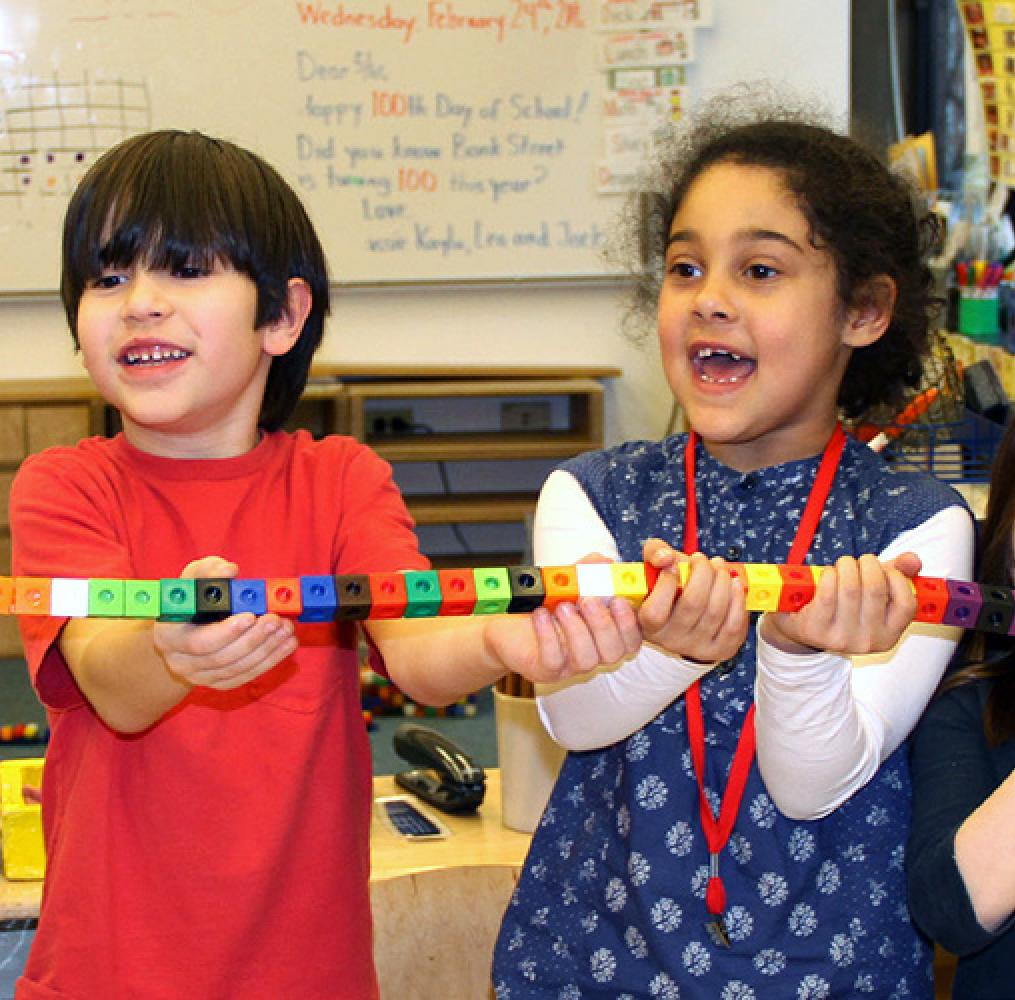 Elementary aged students holding a chain of blocks