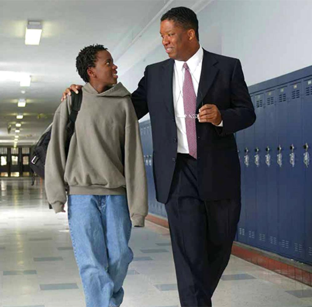 Male educator and male high school-aged student walking in a school hallway