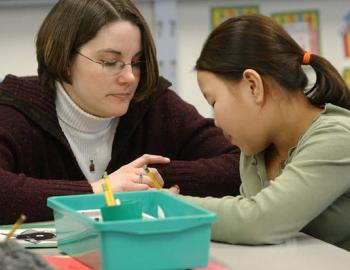 Female teacher with Asian student