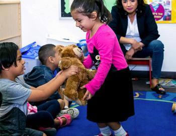 Elementary-aged girl hands a teddy bear to a classmate while a female teacher watches