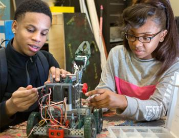 Two high school-aged students working together on building a robot
